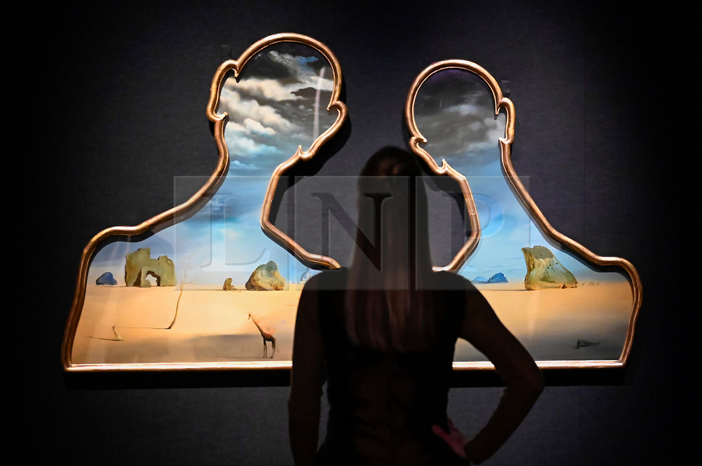 "© Licensed to London News Pictures. 29/01/2020. LONDON, UK.  A staff member poses next to ""Couple aux têtes pleines de nuages"", 1937, by Salvador Dalí (Est. £7-10m).  Preview of Bonhams Impressionist and Modern Art Sale at New Bond Street which will take place on 26 March 2020.  Photo credit: Stephen Chung/LNP"