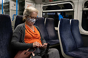 A female rail passenger on a train service through south London wears a facial covering during the Coronavirus pandemic, on 24th August 2020, in London, England.