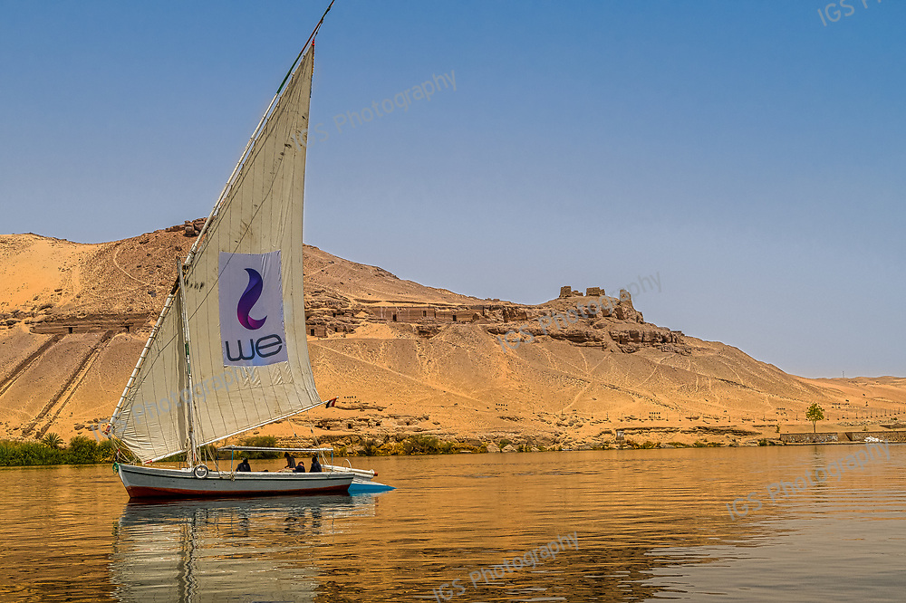 Felucca sailing on the River Nile in Aswan, Egypt. Abo Elhawa tombs and ruins are visible on the west bank