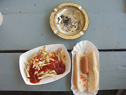 During the Kutztown Folk Festival, Items on a picnic table include an ashtray with a cigarette butt, a partially eaten hot dog with bun, and partially eaten french fries with tomato ketchup.  Kutztown, Pennsylvania.