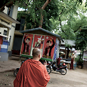 """May 14, 2013 - Mandalay, Myanmar: Ashin Wirathu, the buddhist monk leader of Burma's anti-Muslim movement 969 group, walks by posters of opposition leader Aung San Suu Kyi, in the grounds of Mosayein Monastery in central Mandalay. Wirathu, who was jailed in 2003 for inciting religious hatred, refers to himself as """"the Burmese Bin Laden"""". (Paulo Nunes dos Santos/Polaris)"""