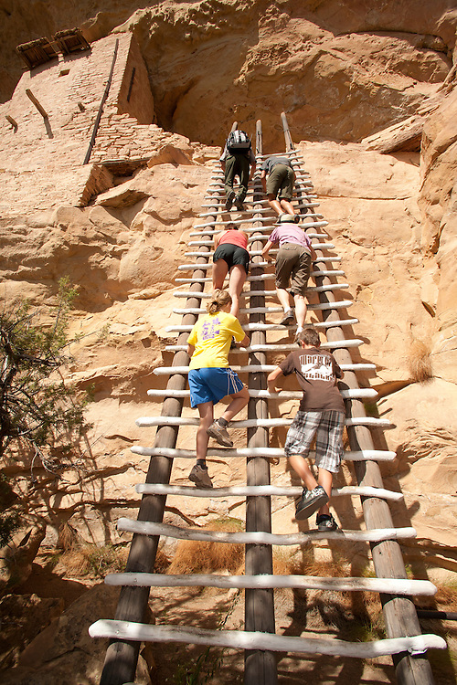 North America, United States, Colorado, Mesa Verde National Park, tourists climbing ladder of Balcony House, an ancient cliff dwelling.  Mesa Verde was home to the Ancestral Pueblo people from approximately 600 A.D. to 1300 A. D. Mesa Verde is Spanish for 'green table.'
