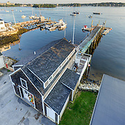 A real estate marketing image taken in very tight quarters, that manages to squeeze in a good view of the building, pier, and setting.
