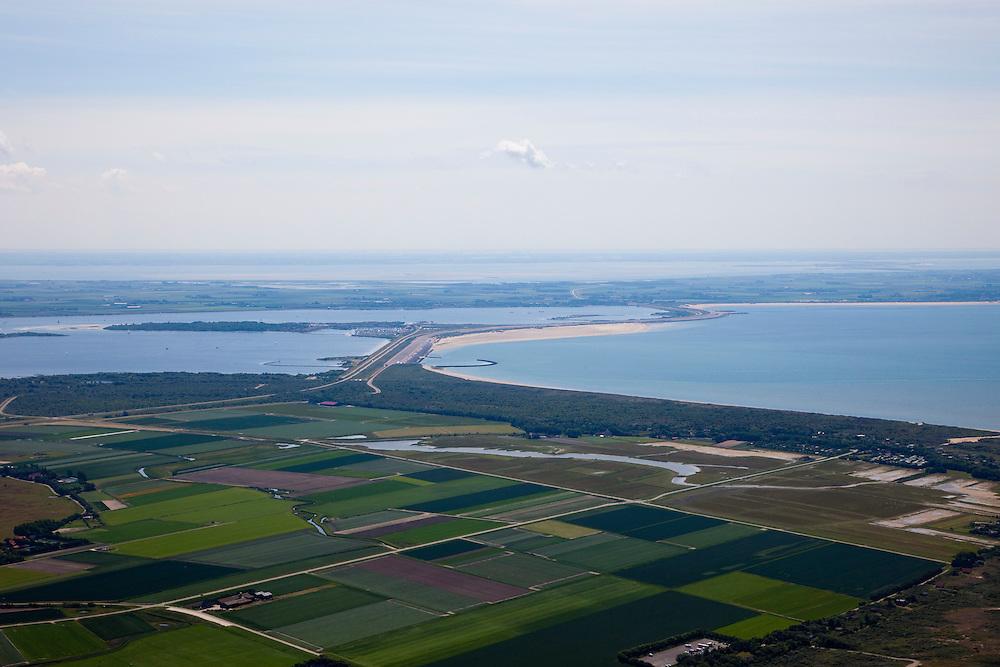 Nederland, Zuid-Holland, Ouddorp, 12-06-2009; de Brouwersdam, onderdeel van de Deltawerken (1971), tussen Goeree en Schouwen (aan de horizon, provincie Zeeland). Links het Grevelingenmeer en in het midden Middelplaat met recreatiecentrum en vakantiepark Port Zelande. In de verte de Oosterschelde, rechts de Noordzee. <br /> Na het afsluiten van de zeearm Grevelingen zijn gaandeweg ernstige milieuproblemen in het nieuwe zoetwater ontstaan. De reeds in 1978 extra gebouwde doorlaatsluis, de Brouwerssluis (bij de uitstulping), heeft onvoldoende verlichting gebracht, er zijn nu plannen om een opening in de dam te maken om zo het getij deels terug te laten keren.<br /> Brouwers dam between the islands Goeree en Schouwen (at the horizon). Left Grevelingen (confluent Meuse Rhine), Northsea to the right, Eastern Scheldt at the horizon.<br /> luchtfoto (toeslag op standaard tarieven);<br /> aerial photo (additional fee required);<br /> copyright foto/photo Siebe Swart.