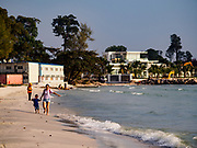 """12 FEBRUARY 2019 - SIHANOUKVILLE, CAMBODIA: Chinese tourists run down the beach near the Blue Bay resort development. Blue Bay is a Chinese casino and resort being built in Sihanoukville. There are about 50 Chinese casinos and resort hotels either open or under construction in Sihanoukville. The casinos are changing the city, once a sleepy port on Southeast Asia's """"backpacker trail"""" into a booming city. The change is coming with a cost though. Many Cambodian residents of Sihanoukville  have lost their homes to make way for the casinos and the jobs are going to Chinese workers, brought in to build casinos and work in the casinos.       PHOTO BY JACK KURTZ"""