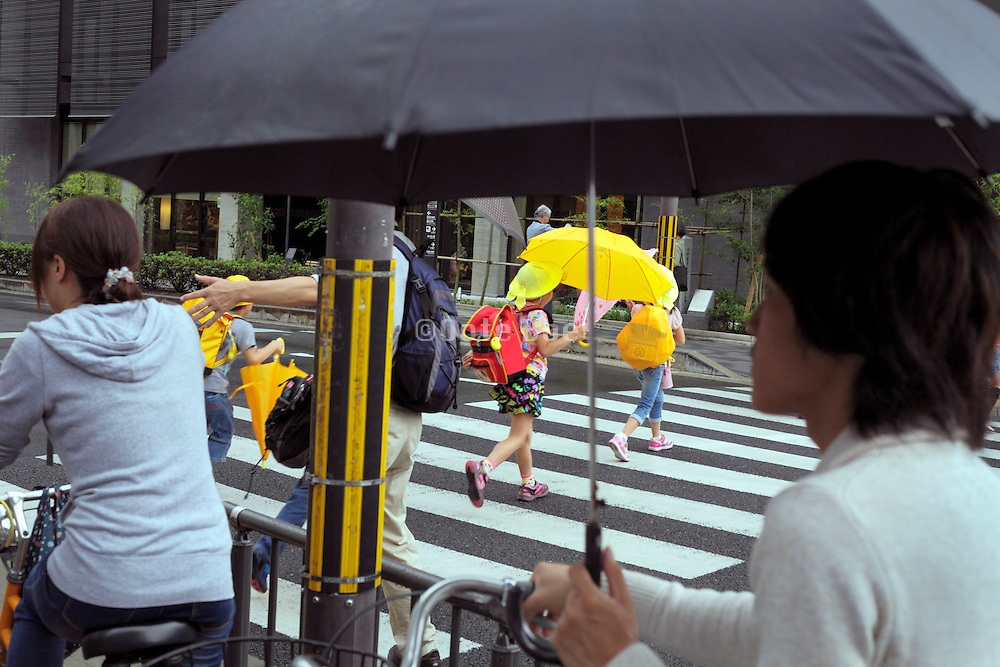 little school children crossing the street with bright colored umbrellas Japan
