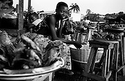Girl selling smoked fish on the roadside.