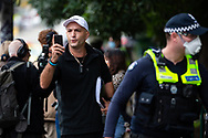 A man verbally attacks police officers while filming the entrance of 120 Racecourse Road amid the third full day of the total lockdown of 9 housing commission high rise towers in North Melbourne and Flemington during COVID 19.After recording 191 COVID-19 cases overnight forcing Premier Daniel Andrews to announce today that all of metropolitan Melbourne along with one regional centre, Mitchell Shire will once more go back to stage three lockdowns from midnight Wednesday June 8. This comes as the residents of the housing commission towers in North Melbourne and Flemington finish their third day under extreme lockdown, despite only 27 cases being found in the towers. Members of the public gathered outside of the towers this afternoon in support of those trapped inside while riot police arrested two women for standing too close to the fence. While the women were later released, tensions are boiling over both in the towers and out. With 772 active cases in Victoria, NSW closed their border to Victoria effective at midnight tonight.