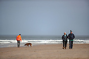 People walk alongside the sand gold beach of Bamburgh on Wednesday, March 17, 2021. Bamburgh is home to the most important Anglo-Saxon archaeological sites in the world, the Bamburgh Castle. (Photo/ Vudi Xhymshiti)