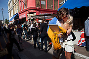 A couple stop to kiss on Portobello Road market, Notting Hill, West London, UK. This famous Saturday market is when the antique stalls line the streets as well as the food stalls further down the hill. This is classic London with busy crowds of people coming to hang out, maybe buy something, or just browse the stalls and have some food.