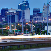 Downtown Kansas City skyline at dawn taken from Front Street in East Bottoms industrial area with traffic motion blur.