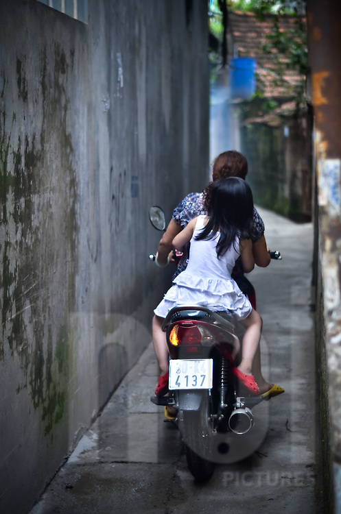 In a tiny alley of Hanoi, a little girl is on the back of a motorbike. She doesn't wear helmet.
