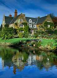 View over lake towards the house at Coton Manor