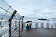 recreational fishing on a wet day at Umikaze park, Yokosuka with Tokyo Bay and Sarushima Island