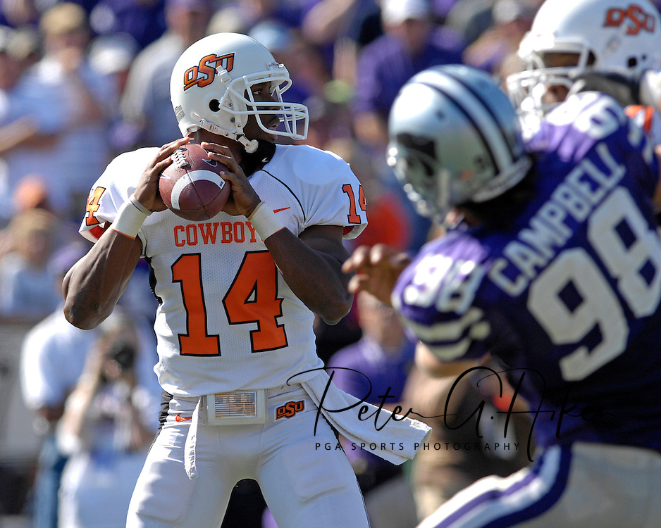 Oklahoma State quarterback Bobby Reid (14) drops back to pass against pressure from Kansas State defensive end Ian Campbell (98)at Bill Snyder Family Stadium in Manhattan, Kansas, October 7, 2006.  The Wildcats beat the Cowboys 31-27.<br />