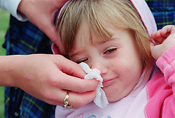 Portrait of girl having nose wiped with tissue,