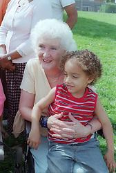 Grandson sitting on grandmother's knee,