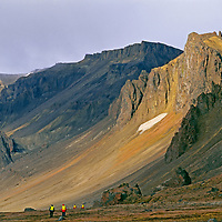 Ecotourists hike over tundra below mountains at Cape Tegetthoff.