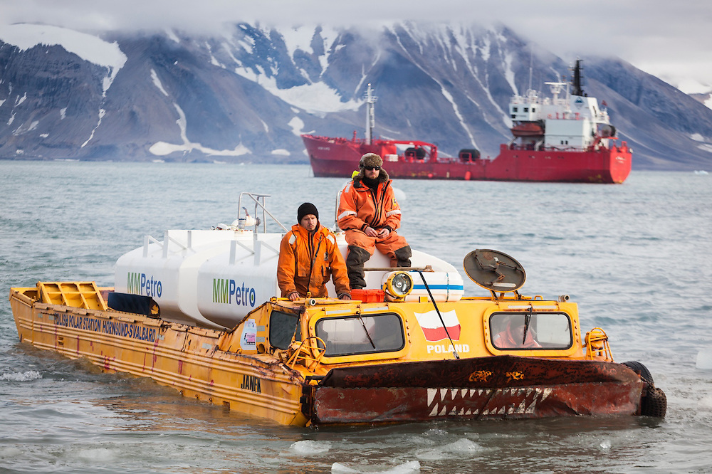 Lukasz Gryglicki, Krysztof Herman, and Robert Zmuda operate a Soviet-era amphibious vehicle to shuttle gasoline from a delivery ship to the storage tanks on land at the Polish Polar Station in Hornsund, Svalbard. The station operates year round and uses 90,000 liters of gasoline per year to operate generators, boats, snowmobiles, and heavy machinery.