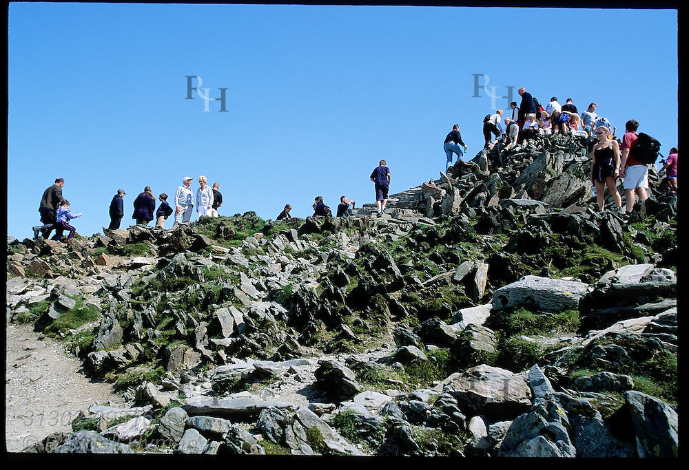 Hikers and railway passengers swarm atop rocky summit of Mount Snowdon (3560'); Snowdonia National Park, Wales.