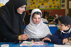 Teacher helping pupils in a lesson at the Nottingham Islamia school,