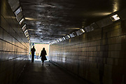 Pedestrians walk through a undepass in Romford, Essex.