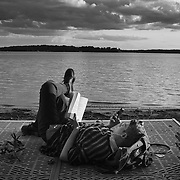 A camper reads from his phone while holding a book along the beach at Green lake at Interlochen Center for the Arts in interlochen, Michigan.