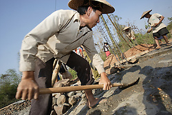 Concrete to mix and shovel keeps the village busy for hours, but finally it is in. Village Had Mad, Pak Ou district Luang Prabang Province. Lao PDR