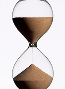 Close up of a hourglass with half the time gone, photographed against a white background