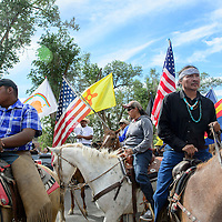 072114  Adron Gardner/Independent<br /> <br /> Leland Grass, right, leads supporters to the Navajo Nation Tribal Council chambers to protest horse roundups and also the proposed Rangeland Improvement act  the start of the summer session of the Navajo Nation Tribal Council in Window Rock Monday.