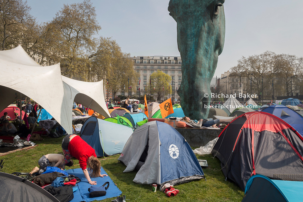 The tents of activists with Extinction Rebellion occupy Marble Arch about climate change beneath the sculpture entitled Horse by Nic Fiddian-Green, on 17th April 2019, in London, England.