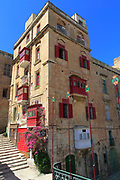 Red balconies and shutters historic building in city centre of Valletta, Malta