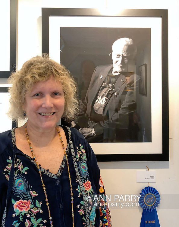 """Manhasset, New York, U.S., September 8, 2019. Ann Parry poses next to her photo """"Buzz Aldrin"""" - the 1st Place winner of The Art Guild's """"About Face: The Portrait"""" juried competition, at Elderfields. photo courtesy Bob Stuhmer"""