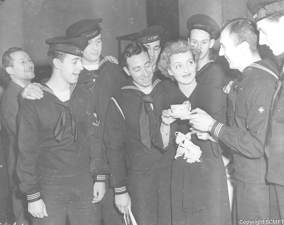 1945 Bette Davis is handed a cup of coffee by a group of sailors