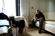 An inmate is sitting on his bed inside one of the private prison cells built with en-suite bathroom and various other amenities in the luxurious Halden Fengsel, (prison) near Oslo, Norway.