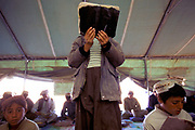 Boy reads his Koran Boys in an Internally Displaced Persons Camp (IDP) called Zahri Dosht