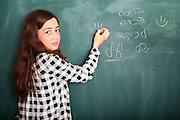 Young pre-teen girl of 12 writes in Hebrew on a blackboard