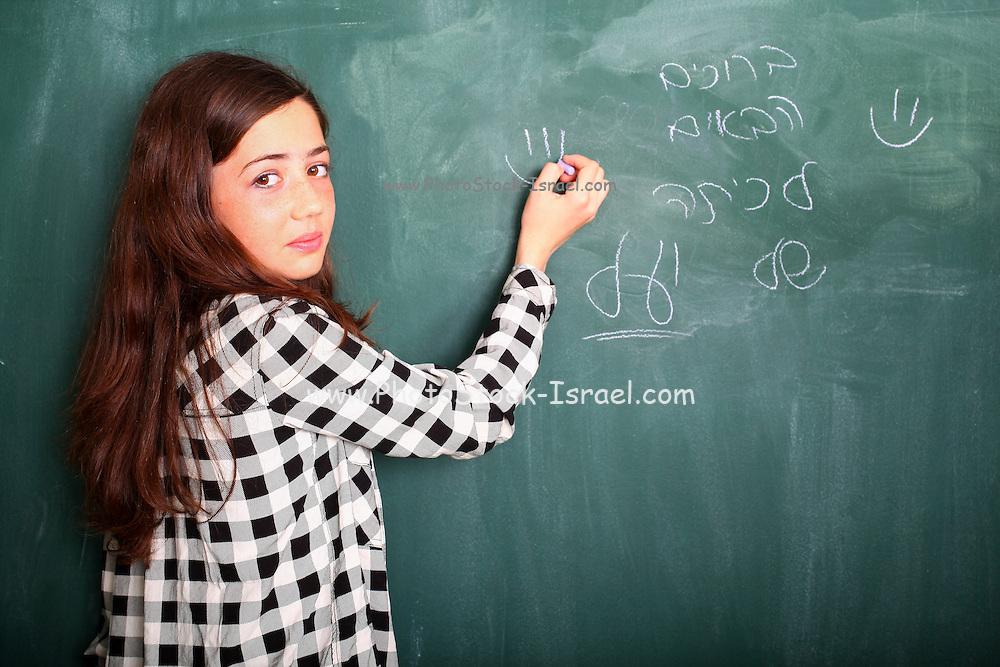 Young pre-teen girl of 12 writes in Hebrew on a blackboard
