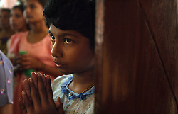 A young girl from the small Christian village Dutch Bar prays during mass at the neighboring St. Mary's Church, Batticaloa, Sri Lanka, Jan. 26, 2005. Residents of the village spent more than six weeks in a makeshift refugee camp at St. Cecilia's Convent recovering from the devastating tsunami that hit the eastern and southern borders of Sri Lanka. They were then moved into another temporary living camp, while awaiting the building of new homes. More than 150 members in this community of less than 1000 people died in the tragic event.