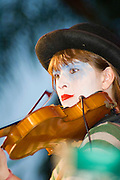 Musician dressed and made up as a clown playing a violin on stage