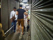 23 FEBRUARY 2018 - BANGKOK, THAILAND: People walk down an aisle lined with shuttered shops in Pratunam Market. Pratunam Market was one of the largest clothing markets in Bangkok. New airconditioned markets, like Platinum and Palladium malls opened nearby, siphoning away customers. Now there are only a handful of merchants left in the market and Bangkok city officials have plans to shut the market and redevelop the land.    PHOTO BY JACK KURTZ