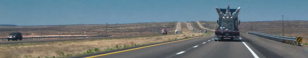A tractor trailer truck hauling large electric transformers cruises west on rural interstate 20 in New Mexico, USA  panorama