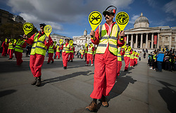 © Licensed to London News Pictures. 09/10/2019. London, UK. Extinction Rebellion protesters dressed as aircraft landing crew take part in a third day of demonstrations in Trafalgar Square in central London. The climate change group intend to blockade the Westminster area for two weeks to demand that the government takes immediate and decisive action on climate change. Photo credit: Peter Macdiarmid/LNP