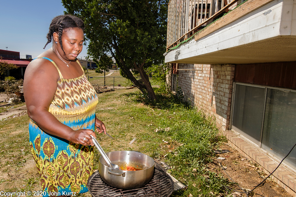 18 AUGUST 2020 - CEDAR RAPIDS, IOWA: PIERRELINE DESPINASSE cooks lunch on a grill in front of her building at Cedar Terrace Apartments in Cedar Rapids. The complex was destroyed by the derecho wind storm. Most of the tenants in the complex are refugees from Africa and Micronesia who have chosen the camp in front of the buildings rather than move to shelters because they're worried about looters taking their belongings. Cedar Rapids was the state's hardest hit city by the derecho that roared across Iowa last week. City officials said the damage left by the derecho was more extensive than the 2008 flood that destroyed much of its downtown. City residents are reporting that almost every home was damaged in the storm, many businesses were closed, and up to half of the city's tree canopy was destroyed. A week after the storm, more than 40,000 homes were still without power. A spokesman for Alliant Energy said the utility has replaced as many power poles in one week that they normally replace in 8 months. On Monday, President Trump approved a $4 billion emergency declaration for Iowa to aid in derecho recovery.    PHOTO BY JACK KURTZ
