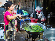 31 DECEMBER 2015 - BANGKOK, THAILAND: A street food cook prepares morning glory (Ipomoea Aquatica), a common Thai green, in Bang Chak Market. The market is supposed to close permanently on Dec 31, 2015. The Bang Chak Market serves the community around Sois 91-97 on Sukhumvit Road in the Bangkok suburbs. About half of the market has been torn down. Bangkok city authorities put up notices in late November that the market would be closed by January 1, 2016 and redevelopment would start shortly after that. Market vendors said condominiums are being built on the land.          PHOTO BY JACK KURTZ