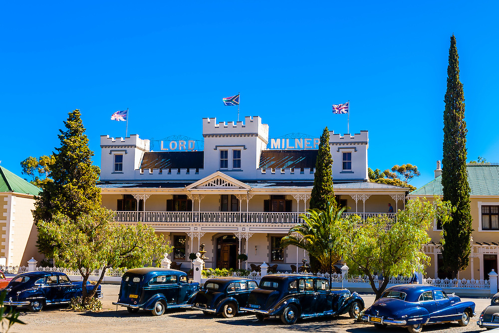 """Lord Milner Hotel, with vintage cars in front, Matjiesfontein. Rovos Rail train """"Pride of Africa"""" on it's journey between Pretoria and Cape Town, South Africa."""