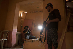 Licensed to London News Pictures. 01/04/2017. Mosul, Iraq. Iraqi Federal Police officers take cover as Islamic State fighters, around 175 metres away, fire at their position in West Mosul, Iraq, today (01/04/2017). Iraqi forces continue to fight house to house as they push further into West Mosul. Iraqi forces are now advancing on the city's old districts where Islamic State fighters still hold out. Photo credit: Matt Cetti-Roberts/LNP
