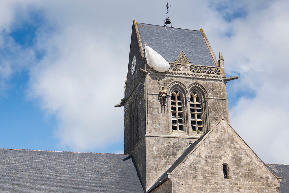 May 30, 2019, Sainte-Mère-Église, Normandy, France.<br /> From the steeple of the village church hangs a parachute with an effigy of Private Steele in his Airborne uniform. <br /> 30 Mai 2019, Sainte-Mère-Église, Normandie, France. Clocher de l'église avec parachute et effigie du soldat Steele.