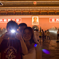 Asia, China, Beijing, Tourists take snapshots in front of portrait of Mao Zedong at the Gate of Heavenly Peace in the Forbidden City at dusk on summer evening