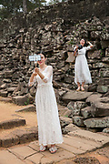 A Chinese women take a selfie photo from her phone dressed in white bridal dresses standing by the ancient ruins of Angkor Thom, Siem Reap Province, Cambodia, South East Asia. A second woman, also dressed as a bride, stands on the stone wall with a DSLR camera.